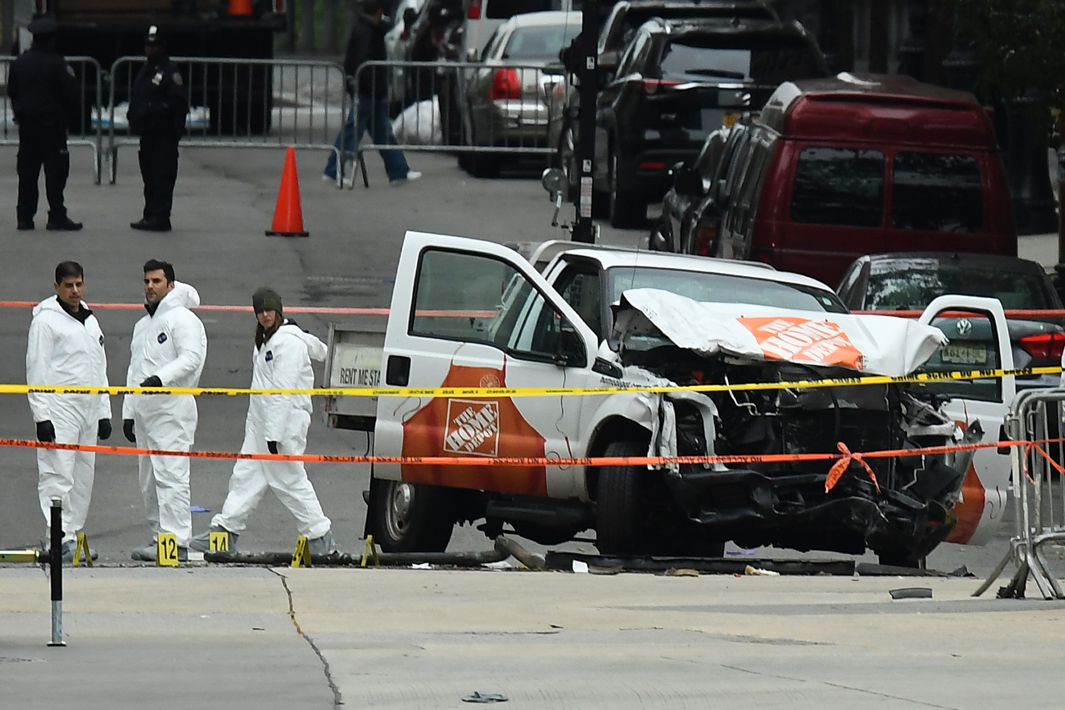 Investigators work around the wreckage of a Home Depot pickup truck a day after it was used in a terror attack in New York on November 1, 2017. The pickup truck driver who plowed down a New York cycle path, killing eight people, in the city's worst attack since September 11, was associated with the Islamic State group but